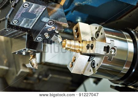 metalworking  industry: cutting tool processing bronze metal detail on lathe machine in factory workshop