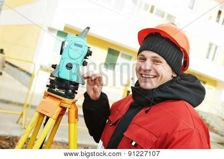 Surveying industry: smiling positive surveyor working with theodolite transit equipment at construction site