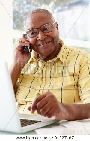 Senior Man On Phone Using Laptop At Home