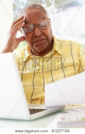 Worried Senior Studying Paperwork At Home