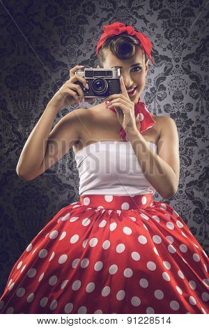 Vintage style - Woman using an old camera in polka dots clothes