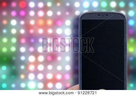 Smatrphone and disco background. Idea for party app, digital detox, taking shots, accessing apps, Internet, blogs and others. The background image is an illustration created by the same author.