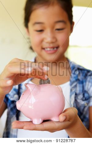 Young girl putting money in piggybank