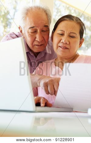Senior Taiwanese couple working on laptop