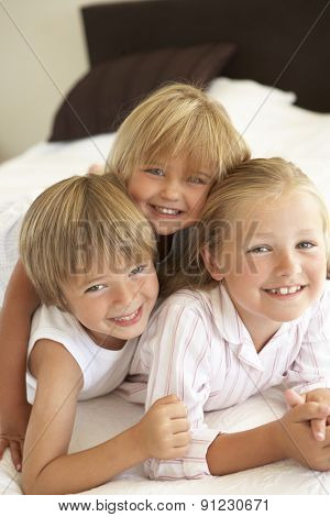 Group Of Children Relaxing On Bed