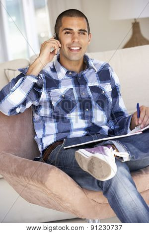 Young Man Doing Paperwork And Using Mobile Phone At Home