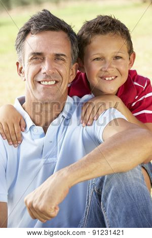 Middle Aged Father And Son Relaxing In Countryside