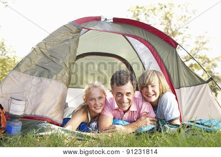 Father With Teenage Children On Camping Holiday In Countryside