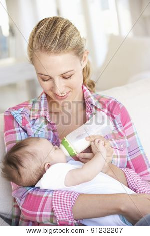 Young Mother With Baby Feeding On Sofa At Home