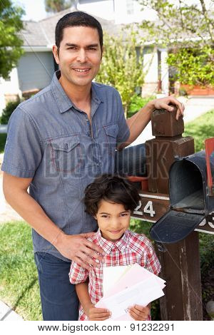 Hispanic Father And Son Checking Mailbox