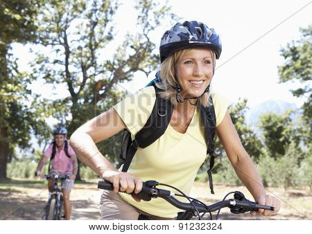 Middle Aged Couple Cycling Through Countryside