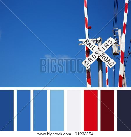 Railroad crossing sign against blue sky background. In a colour palette with complimentary colour swatches.