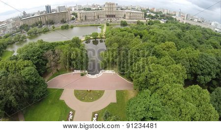 Aerial view of cityscape with houses around pond at summer.