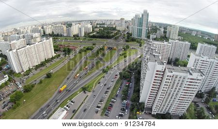 Cityscape with crossroad traffic at summer cloudy day. Aerial view