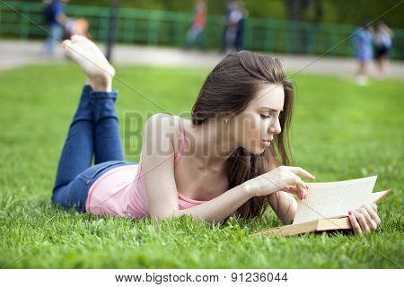 Young beautiful brunette girl with book lying on the green grass in the summer park