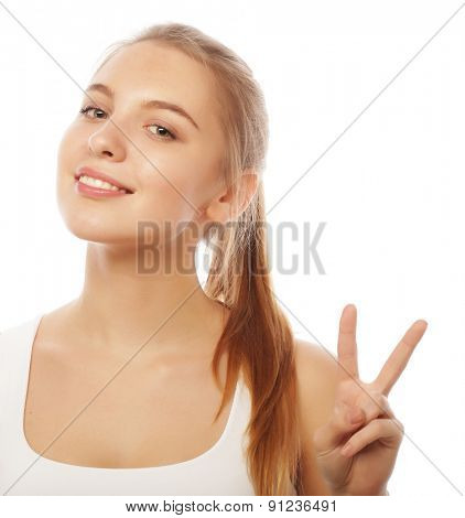 portrait of happy young woman giving peace sign isolated on white background