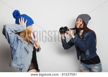 a girl takes picture of her friend in front over white backgrounf