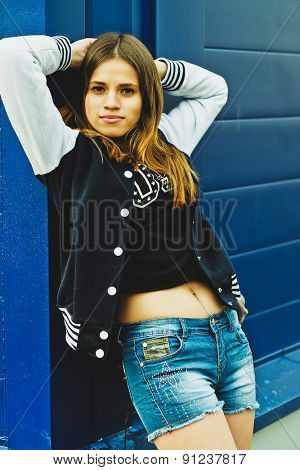 lifestyle portrait stylish hipster girl  against colorful wall in city, street fashion