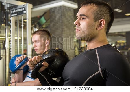 Kettlebell Swing Training Of Two Young Men In The Gym