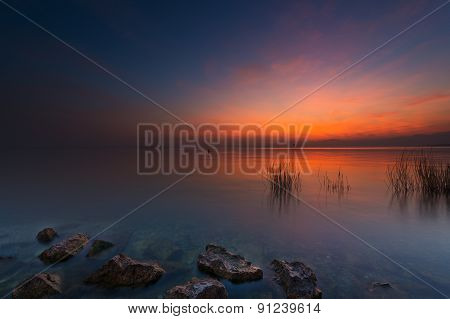 rocks and grass in lake at red orange sunset in italy