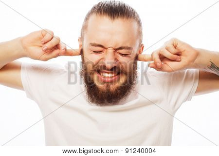 life style and people concept: frustrated bearded man in white shirt holding fingers in his ears and keeping eyes closed while standing against white background