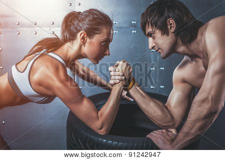 Athlete muscular sportsmen man and woman with hands clasped arm wrestling challenge between a young