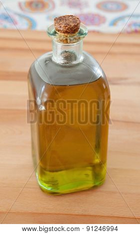 Bottle of golden olive oil on wood