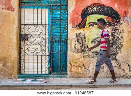 HAVANA,CUBA - MAY 20,2015 : Young cuban man walks by a colorful Che Guevara portrait painted on a shabby  old wall in Old Havana