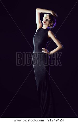 Full length portrait of a fashionable model posing in long black dress over black background. Beauty, fashion.