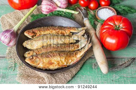 Fried fish and vegetables on the table. Rustic style