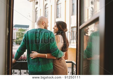 Young Couple Standing At The Balcony Of The Hotel Room
