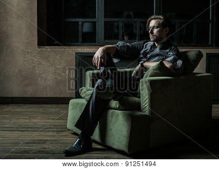 Businessman sitting on an armchair. Fahion man.