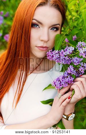 beautiful sexy woman with fiery regime hair with eyes of a Fox in the garden with lilacs