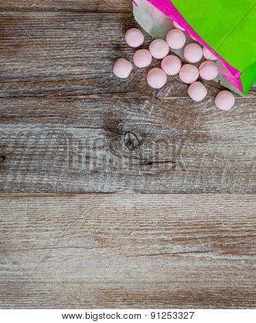 pink candies on a wooden background with space for text