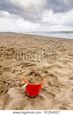 Bucket Full Of Sand On The Beach In A Cloudy Day
