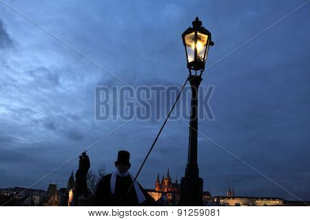 PRAGUE, CZECH REPUBLIC - DECEMBER 5, 2012: Lamplighter lights a street gas light manually during the Advent at the Charles Bridge in Prague, Czech Republic.