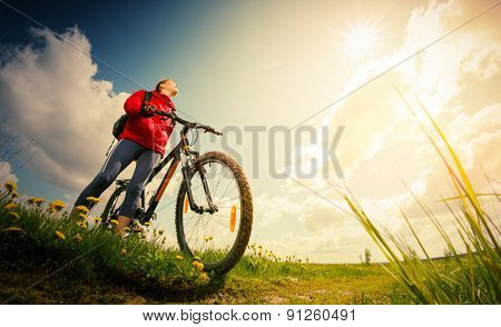 Young lady hiker standing with bicycle on a green summer meadow
