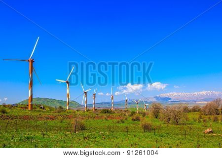 Several huge modern windmills on background snowy Hermon. Flowering Golan Heights on a sunny day. Galilee, Israel