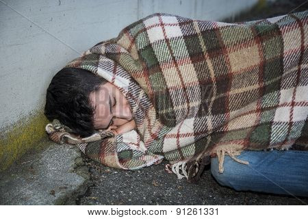 Young male beggar on city sidewalk sleeping