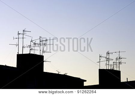 Silhouettes of TV antennas on a roof.