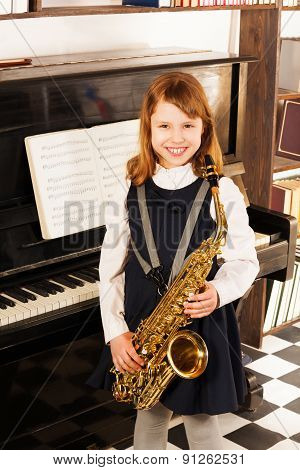 Smiling girl in school uniform with alto saxophone