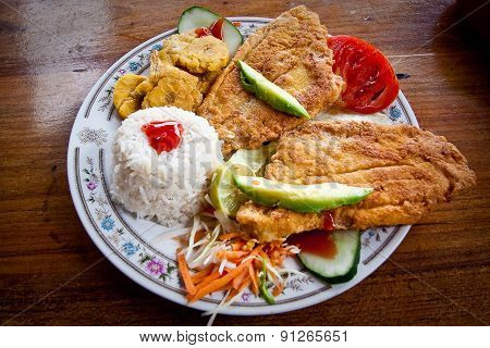 Breaded fish served with rice and plantain chips, traditional ecuadorian dish