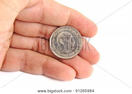 Man hand holding an old Spanish coin of 50 pesetas showing Franco dictator face on a white backgroun