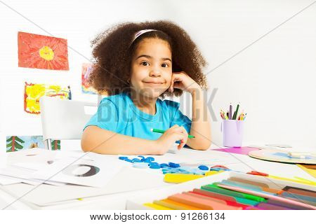 African girl writes letters sitting at table