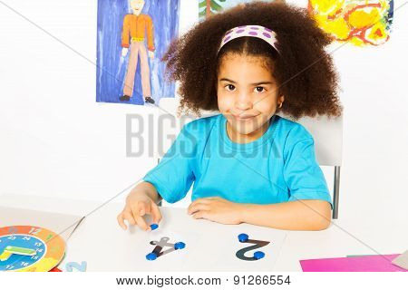 Cute African girl learn numbers with coins
