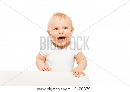 Angry small baby with open mouth in white bodysuit