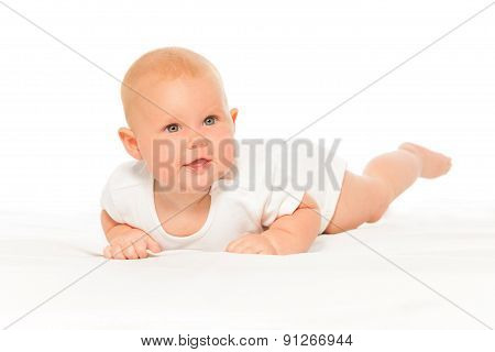 Baby with cheeks in white bodysuit laying alone