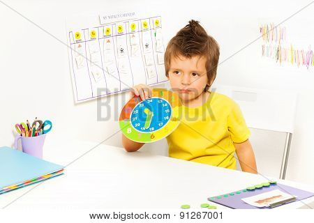 Boy holding carton clock sitting at the table