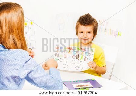 Cute boy holding the drawing with colored shapes