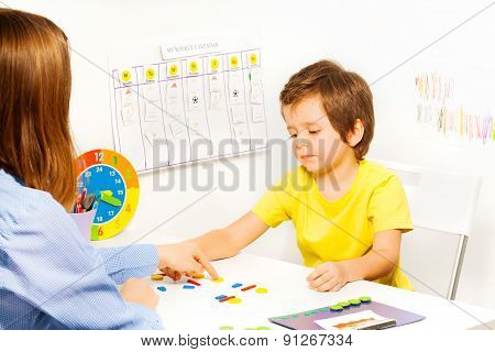 Boy putting colorful shaped coins in order